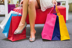 Woman sitting and holding shopping bags Stock Image