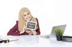Woman sitting and holding a sign in her hands with words THANK YOU. Pretty woman sitting and holding a sign in her hands with words THANK YOU Stock Image