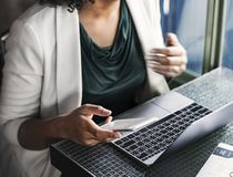 Woman Sitting Holding Smartphone And Facing Laptop stock photography