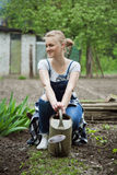 Woman sitting and holding watering can Stock Photos