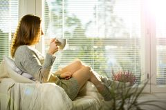 Woman sitting at home in a chair by the window with cup of hot coffee. Wearing knitted warm sweater. Cozy sunny room filled with light. beautiful morning behind royalty free stock photography