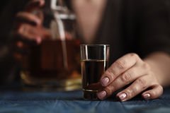 Woman sitting at home drinking way too much whiskey, she is addi Stock Photography