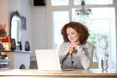 Woman sitting at home and looking at computer Stock Image