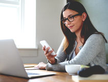Woman sitting in home office checking mobile phone. Woman sitting in home office at desk smirking and checking mobile phone Stock Photos