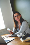 Woman sitting in home office smiling and holding mobile phone. Attractive woman sitting at desk in home office smiling at camera and holding mobile phone stock image