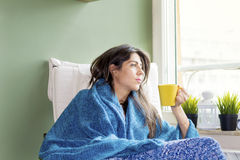 Woman sitting at home ,thinking with tea in hand Royalty Free Stock Photography