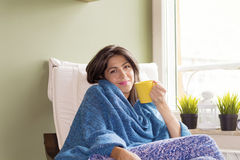 Woman sitting at home ,thinking with tea in hand Royalty Free Stock Image