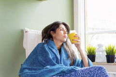 Woman sitting at home ,thinking with tea in hand Royalty Free Stock Photos