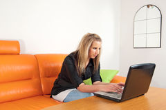 Woman sitting at home using a laptop Royalty Free Stock Image