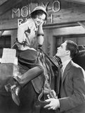 Woman sitting on a horse talking and flirting with a young man Stock Photos