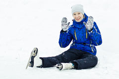 Woman sitting on ice skates. Woman in skates sitting on the ice smiling stock photos