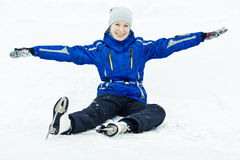 Woman sitting on ice skates. Woman in skates sitting on the ice smiling stock photography