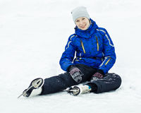 Woman sitting on ice skates. Woman in skates sitting on the ice smiling royalty free stock photography