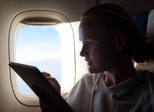 Woman sitting by illuminator in plane with touch Royalty Free Stock Images