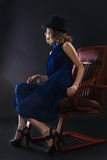 Woman sitting. The image of a beautiful luxurious woman sitting on chair. Studio shot Stock Image
