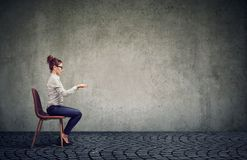 Woman sitting at imaginary table Stock Photography