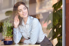 Woman Sitting Indoor In Urban Cafe Looking Through The Window Stock Photography