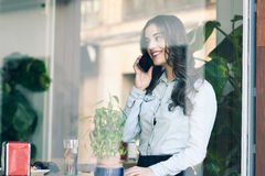 Woman Sitting Indoor In Urban Cafe Looking Through The Window Stock Image