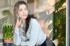 Woman Sitting Indoor In Urban Cafe Looking Through The Window Royalty Free Stock Image