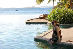 Woman sitting infinity pool. At Likuliku Resort in Fiji stock photography