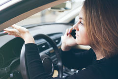 Woman is sitting inside a broken car and calling by phone the wrecker Stock Photo