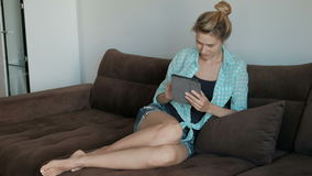 Woman sitting inside her room on bed chat in tablet stock video