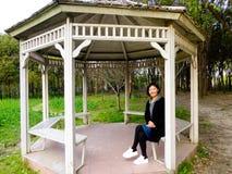 A woman sitting inside a pavilion Stock Image