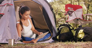 Woman sitting inside the tent and using a digital tablet stock video