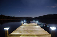 Woman sitting on jetty Royalty Free Stock Image