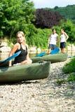 Woman sitting by kayak Stock Photo