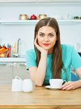 Woman sitting at kitchen with coffee cup. Royalty Free Stock Photos