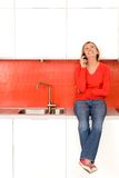 Woman sitting on kitchen counter Royalty Free Stock Photo