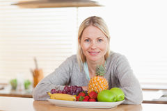 Woman sitting in the kitchen with a plate of fruits Royalty Free Stock Photo