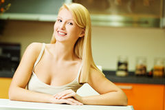Woman sitting at kitchen table Stock Photos