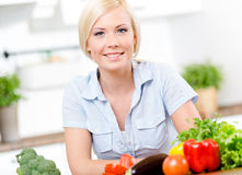 Woman sitting at the kitchen table with groceries Stock Photos