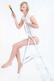 Woman sitting on ladder. With a brush Royalty Free Stock Images