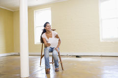 Woman sitting on ladder in empty space Royalty Free Stock Photo