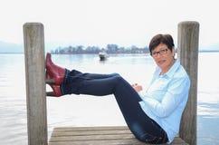 Woman sitting at Lake Chiemsee Royalty Free Stock Image
