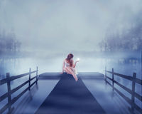 Woman sitting on a lake pier with bright ball of glowing light in her hand Royalty Free Stock Photos