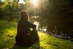 Woman sitting on lake shore Royalty Free Stock Photos