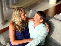 Woman sitting on the lap of man and they both smile. royalty free stock photography