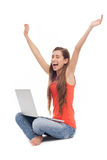 Woman sitting with laptop, arms raised. Young woman over white background Royalty Free Stock Photography