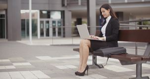 Woman sitting with laptop on bench outdoors stock video footage