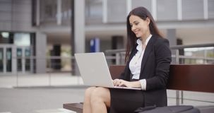 Woman sitting with laptop on bench outdoors stock video