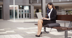 Woman sitting with laptop on bench outdoors. Cute business woman sitting alone on bench in front of office building working on laptop computer Stock Photo