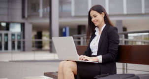 Woman sitting with laptop on bench outdoors. Cute business woman sitting alone on bench in front of office building working on laptop computer Stock Image