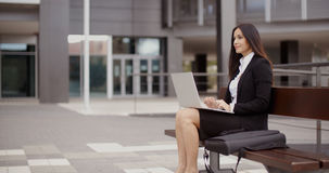 Woman sitting with laptop on bench outdoors. Cute business woman sitting alone on bench in front of office building working on laptop computer Stock Photography