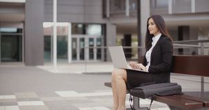 Woman sitting with laptop on bench outdoors stock footage