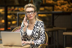 Woman sitting with laptop in cafe, talking on a cell phone. Royalty Free Stock Photo