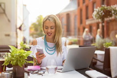 Woman sitting with laptop and chatting on her mobile phone Stock Photo